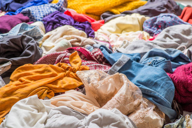 pile of used clothes on a light background. Second hand for recycling stock photo