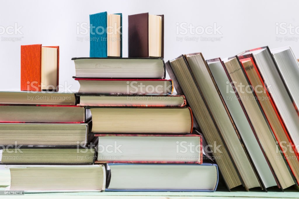 Pile of various books on bright wooden background. royalty-free stock photo