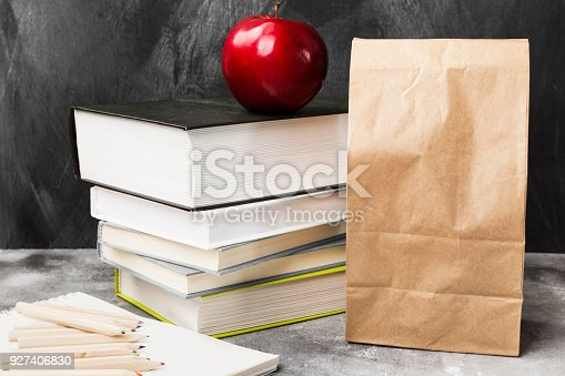 istock Pile of various books, red apple and package of lunch on dark background 927406830