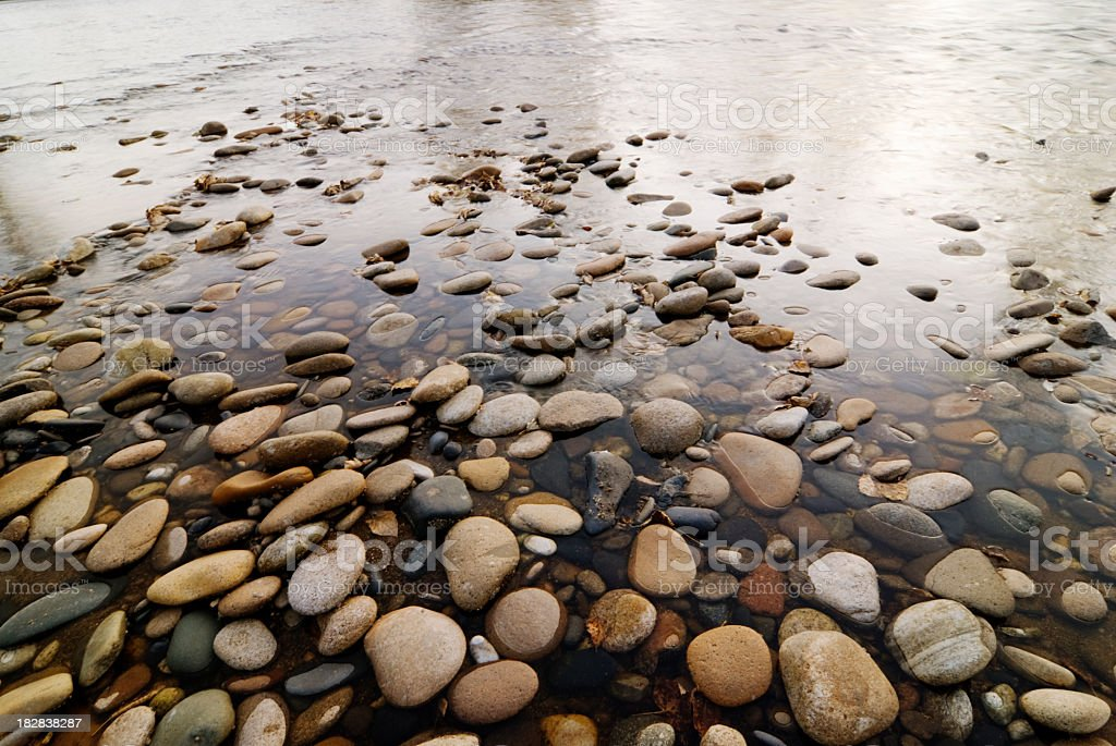 Pile of various colors and sizes of pebbles in water stock photo