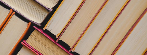 Pile of vintage paper orange books in hard cover. Fall reading list. stock photo