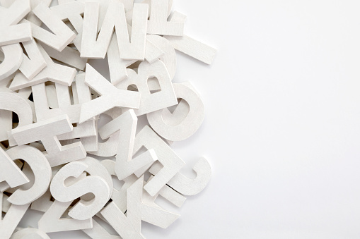 Pile Of White Painted Wooden Letters Typography Background Composition - Fotografie stock e altre immagini di A forma di blocco