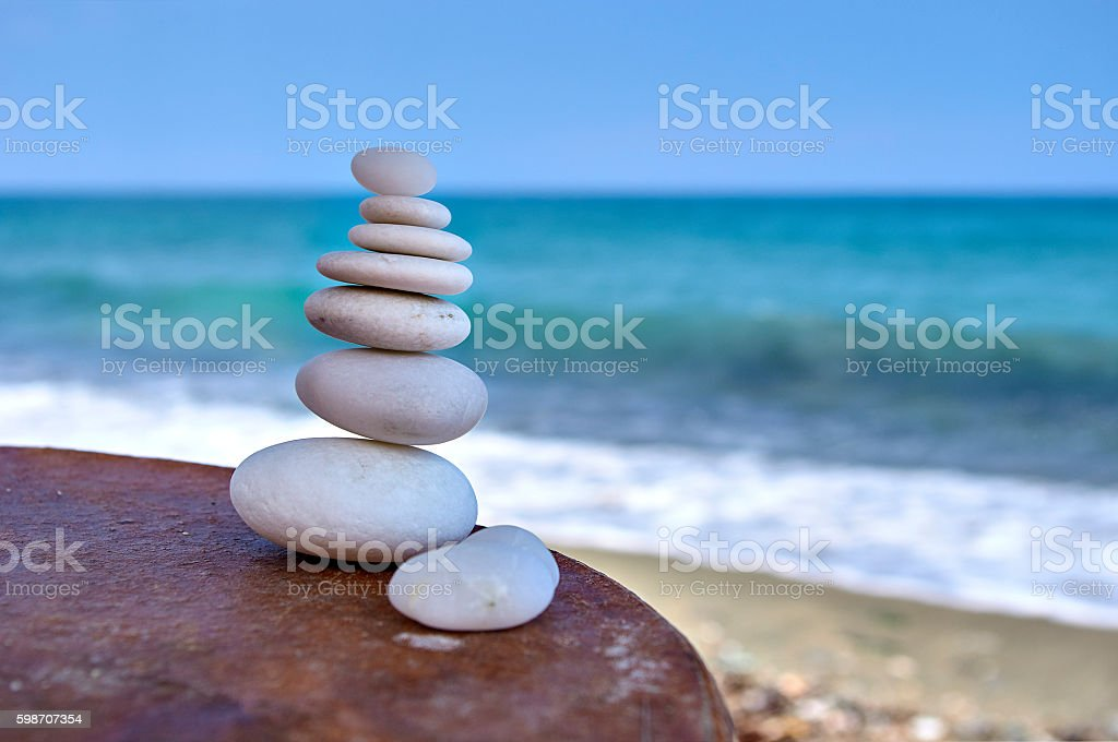 Pile of white rocks on a table near the sea stock photo