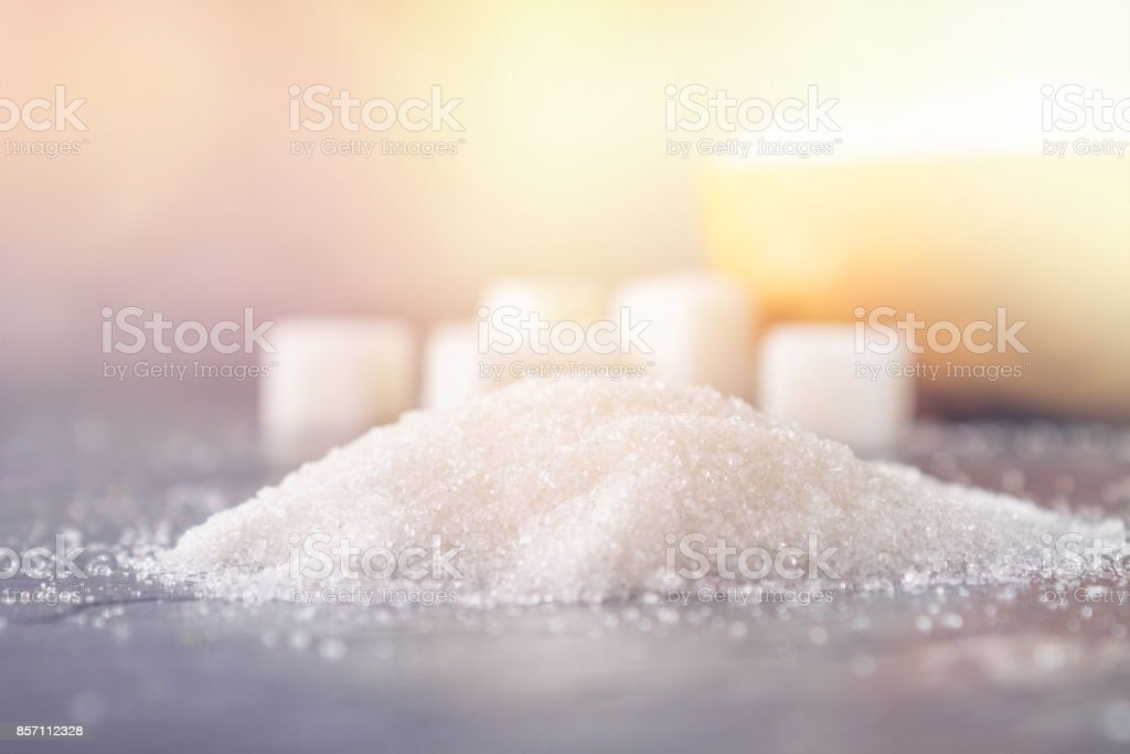 A pile of white sugar on a dark background. stock photo