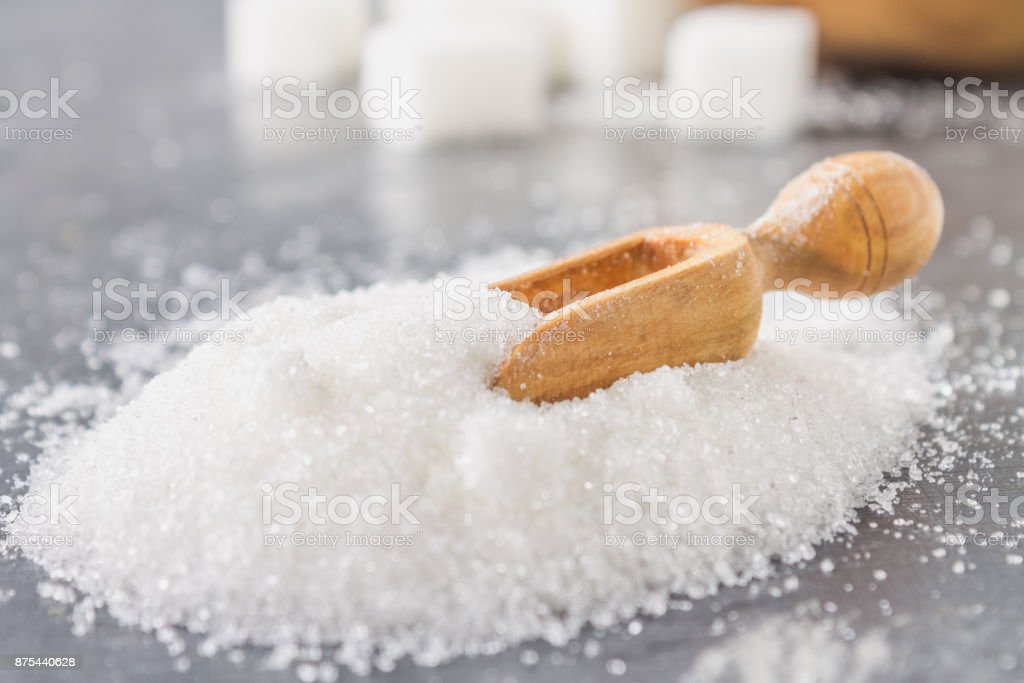 A pile of white sugar sand with a wooden scoop on a dark background. stock photo