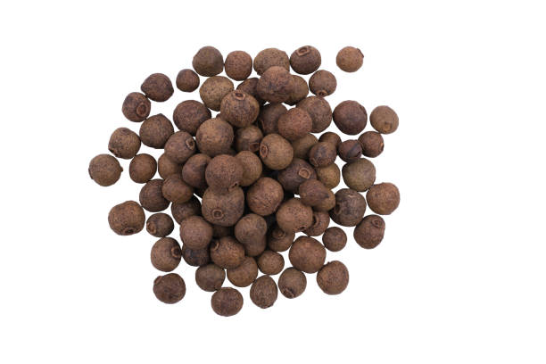 A pile of whole allspice, jamaica peppe isolated on white background A pile of whole allspice, jamaica peppe isolated on white background allspice stock pictures, royalty-free photos & images