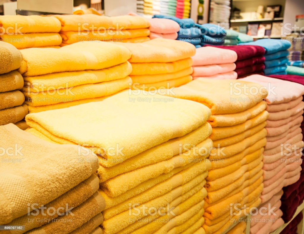 A pile of yellow pink red and blue towels stock photo