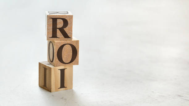 Pile with three wooden cubes - letters ROI meaning Return on Investment on them, space for more text / images at right side. stock photo