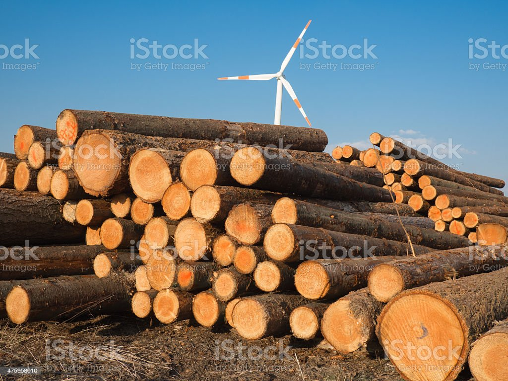 pile wood logs with a wind turbine stock photo