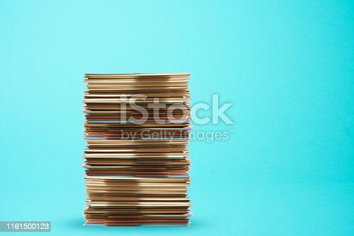 Piled up file folder on light blue background with copy space.