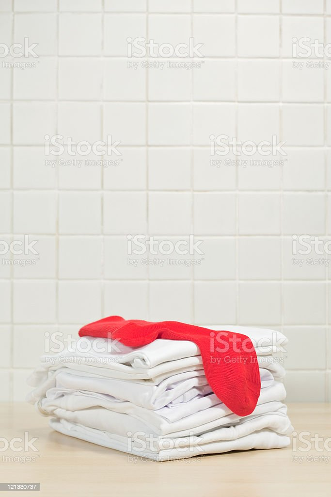 Piles of clean white laundry and red sock stock photo