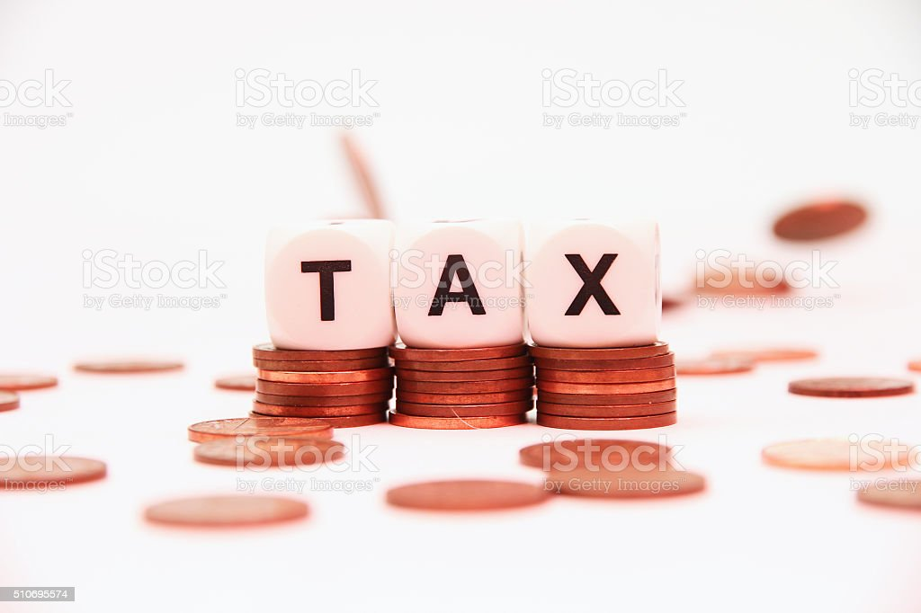 Piles of coins with word tax stock photo