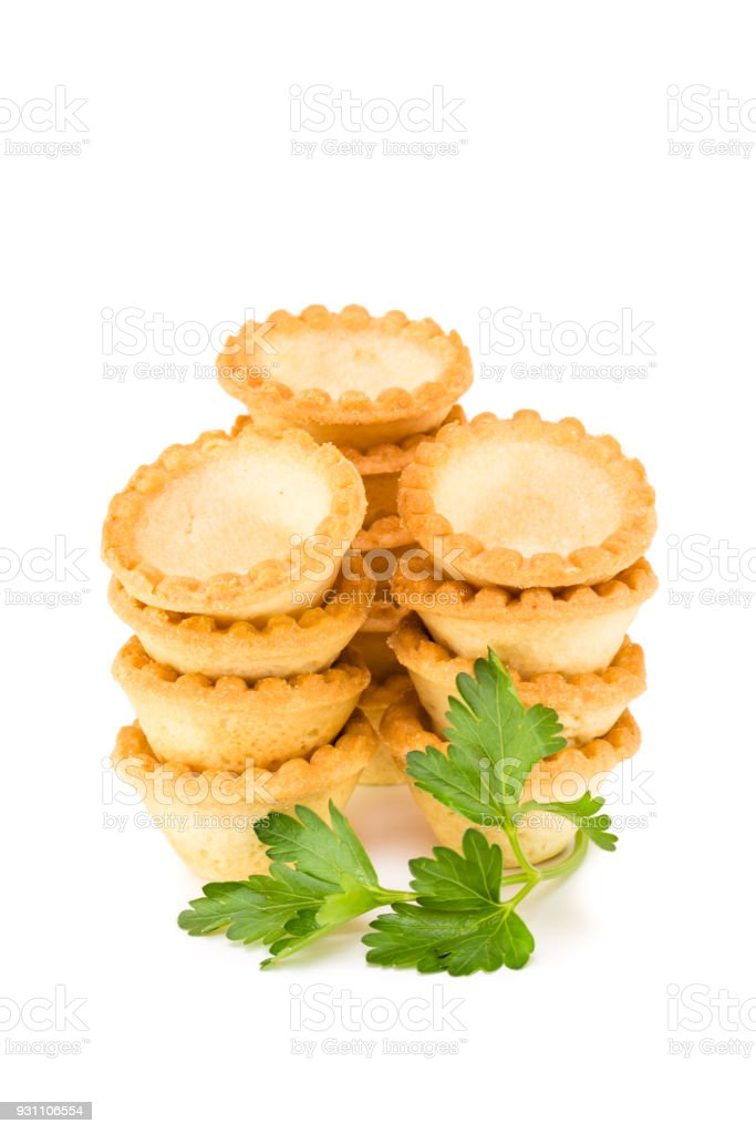 Piles of empty tartlets and a branch of parsley stock photo