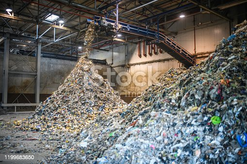 Floor-level action shot of separated recyclables falling from elevated conveyor belt onto growing pile inside waste management facility.