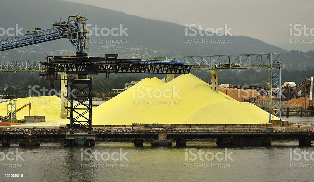 Piles of Yellow Sulphur on Dock at Chemical Processing Factory stock photo