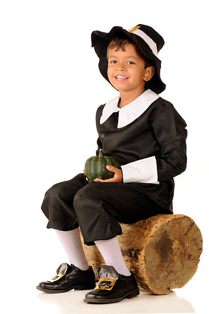 Pilgrim Boy with Squash An adorable preschool-aged Pilgrim holding a green squash while sitting on an old log.  On a white background. pilgrim stock pictures, royalty-free photos & images
