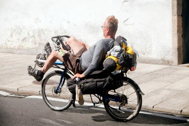 Pilgrim cyclist riding a recumbent bike in old town Santiago de Compostela. stock photo