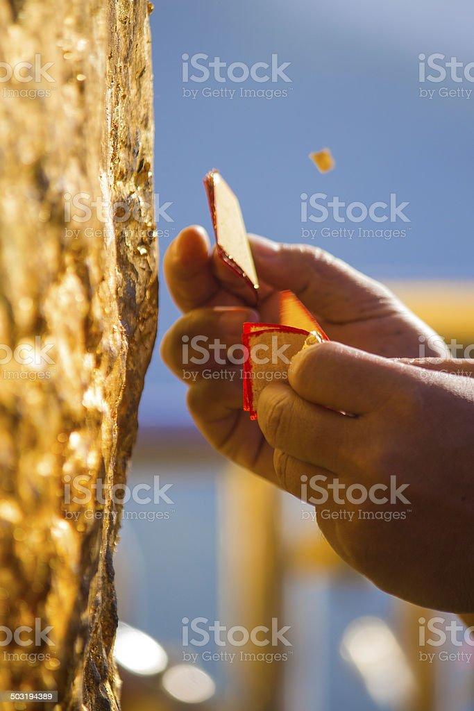 Pilgrim Pasting Gold Leaves at Golden Rock Myanmar stock photo