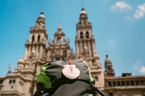 Pilgerrucksack mit berühmtem Pilgermaskottchen und Schild Muschel mit Kreuz des Heiligen Jakobus auf dem Obradeiro Platz (Plaza) - der Hauptplatz in Santiago de Compostela mit Catedral de Santiago. – Foto