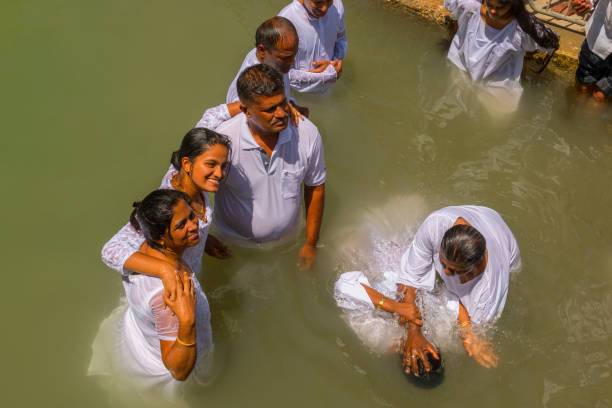 Pilgrims baptizing in the Jordan River, in the Yardenit Baptismal Site. Northern Israel. stock photo