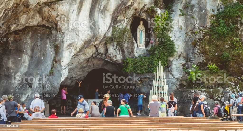 Pilgrims enter the cave of Lourdes, France stock photo