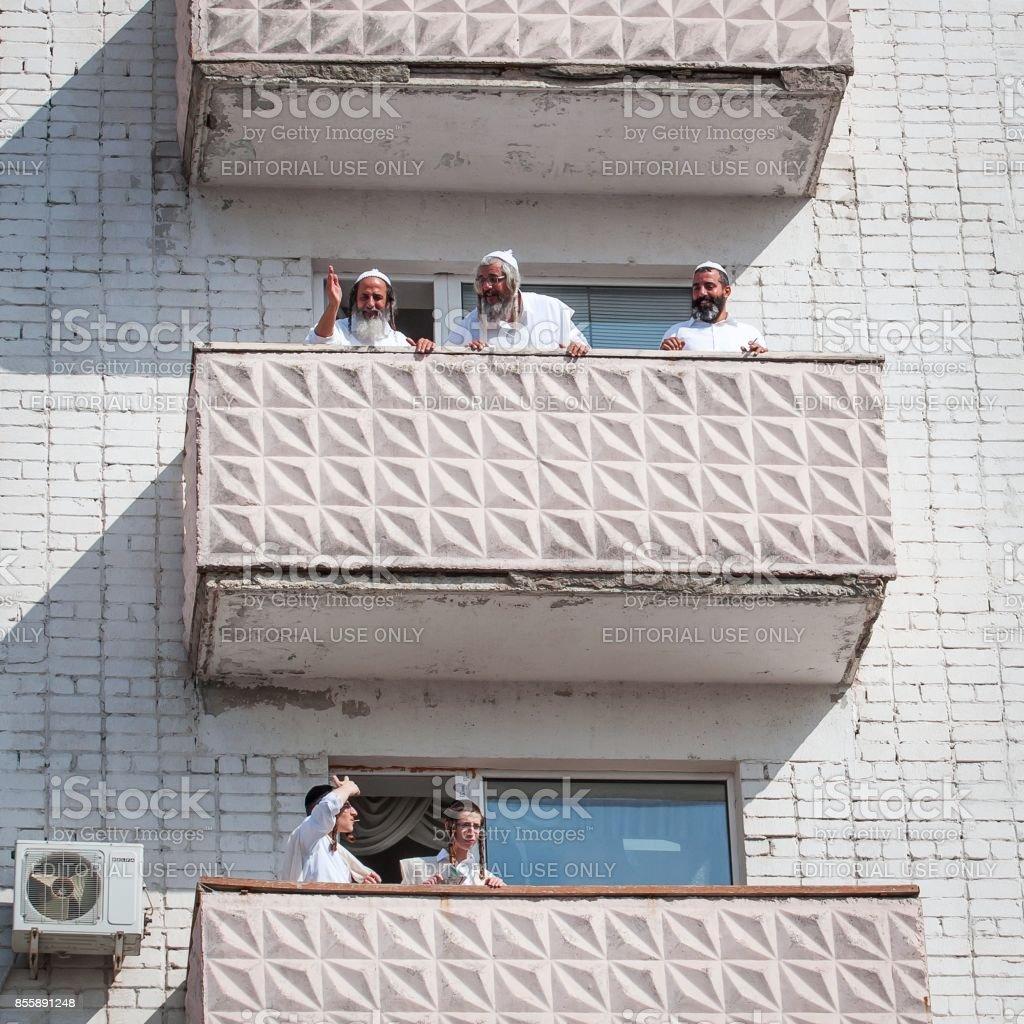 Pilgrims of Hasidi on the balcony of the high-rise building are having fun celebrating the holiday of Rosh Hashana. stock photo