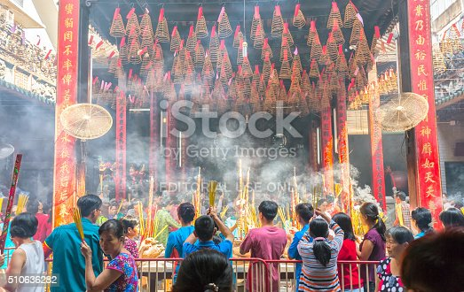 Ho Chi Minh City, Vietnam - February 8th, 2016: Pilgrims pagoda Lunar New Year's Day with hundreds of people holding bouquet of incense tingle slave to pray for peace in the temple joyful atmosphere, the first day bustle in Ho Chi Minh City, Vietnam