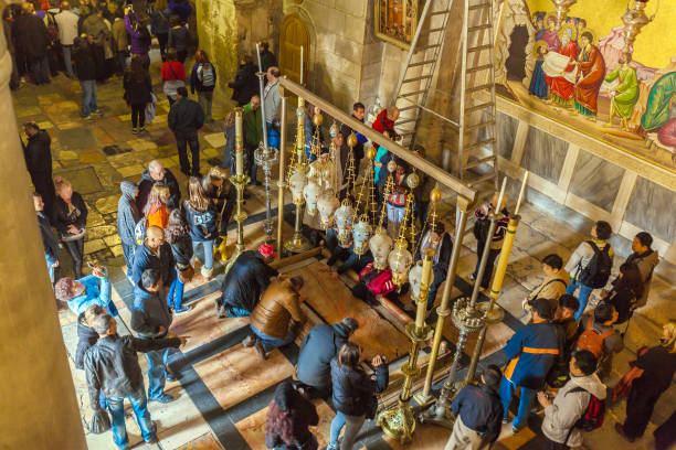 JERUSALEM, ISRAEL - FEBRUARY 16, 2013: Pilgrims praying near Stone of Unction in Church of the Holy Sepulchre stock photo