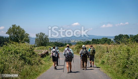 A group of pilgrims walk down a country road that is part of the Camino de Santiago near Portomarin, Spain (July 7, 2018)