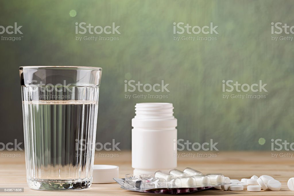 Pill blister packs and glass of clean water stock photo