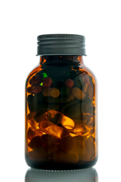 pill bottle filled with colorful pills stock photo