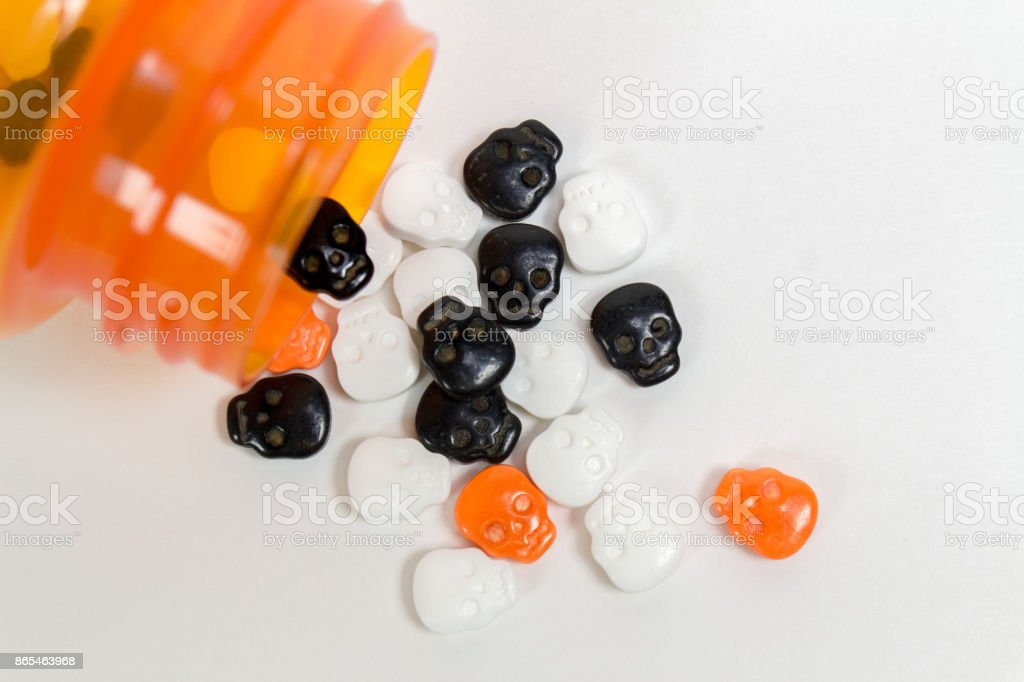 Pill bottle with skull shaped pills spilling out stock photo