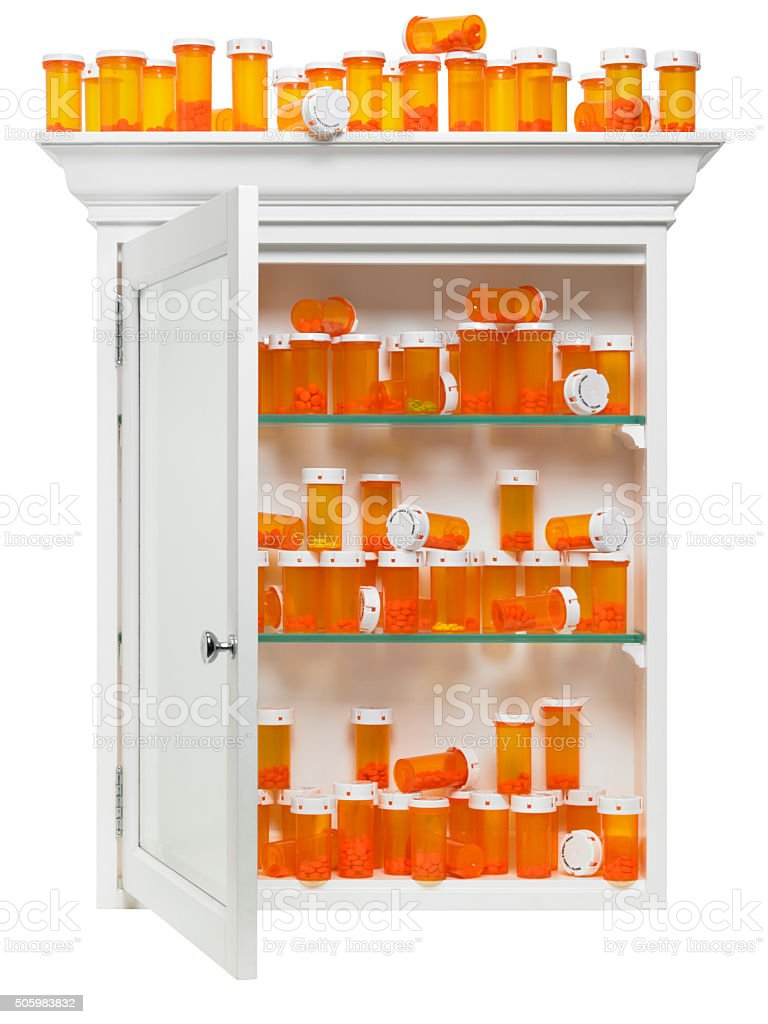 Pill bottles stacked in medicine cabinet isolated on white stock photo