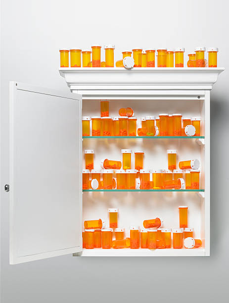 Pill bottles stacked in medicine cabinet stock photo