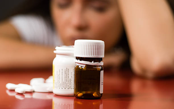 Pill bottles with pills next to them and a woman in back stock photo