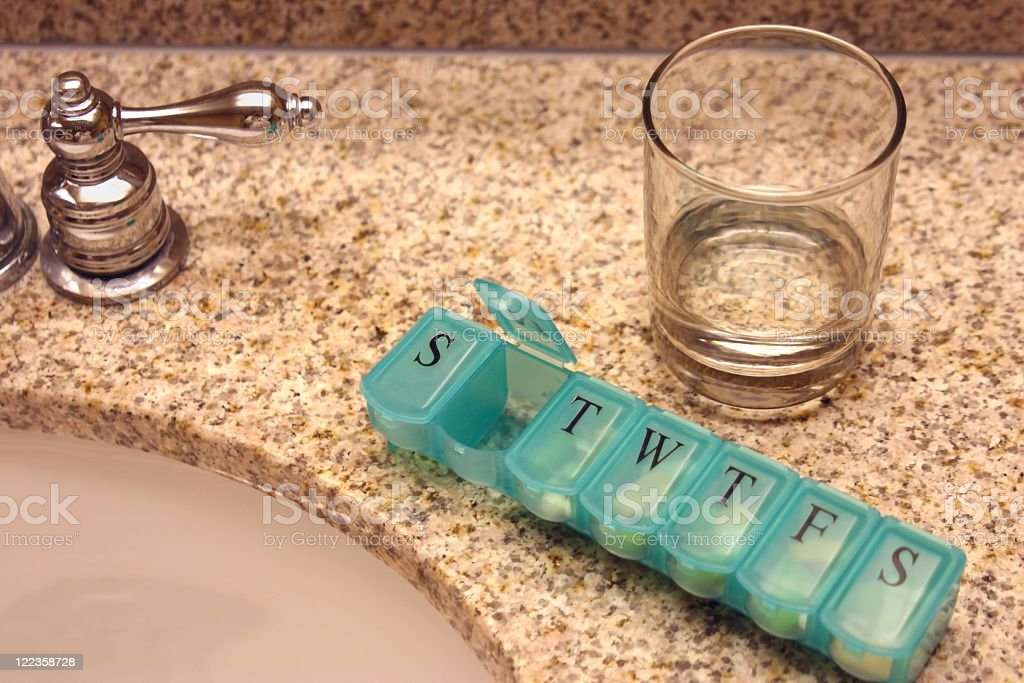 Pill Box by Sink and drinking glass stock photo