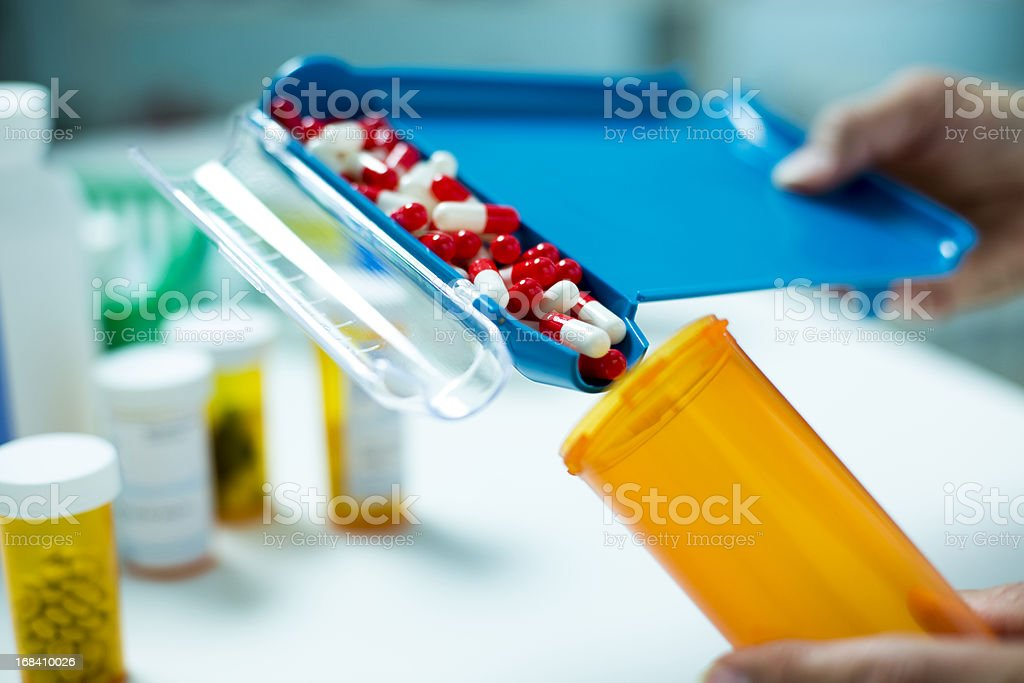 Pill Counter filling Pill Bottle with Capsules stock photo