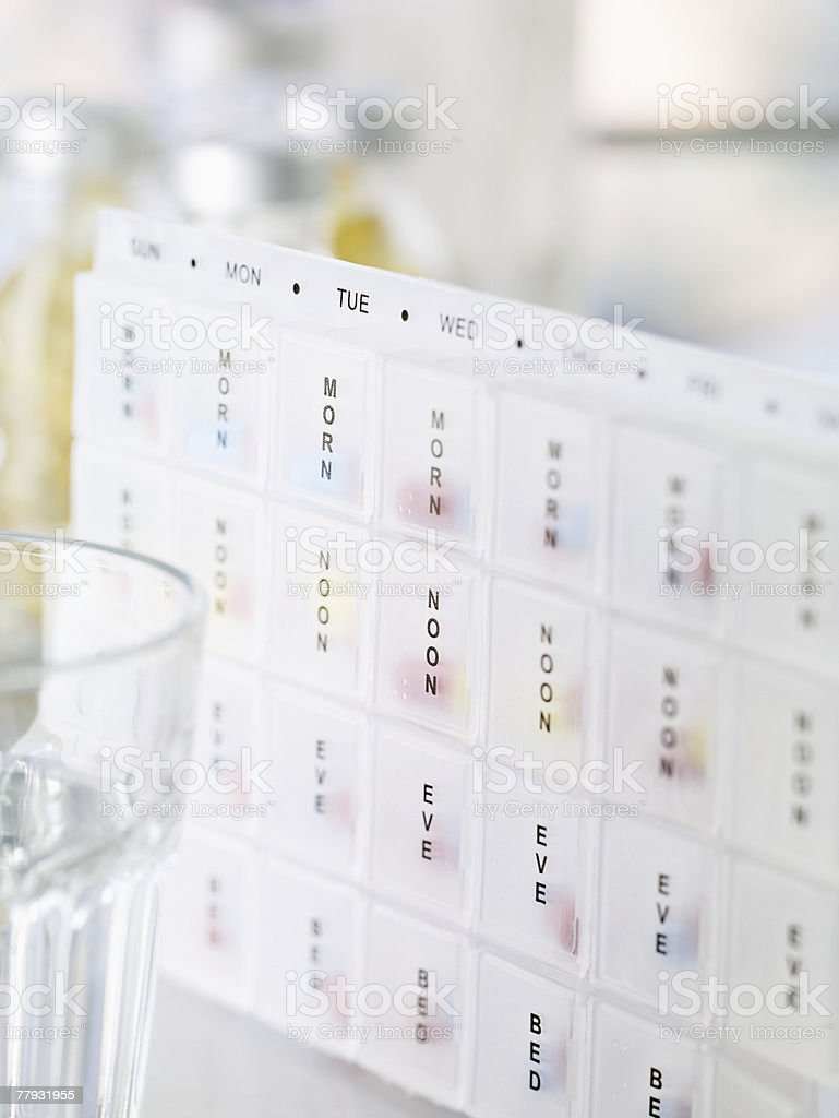 Pill dispenser and a glass of water stock photo