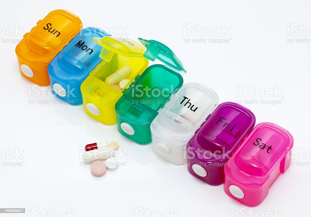 Pill organizer with tablets and capsules stock photo