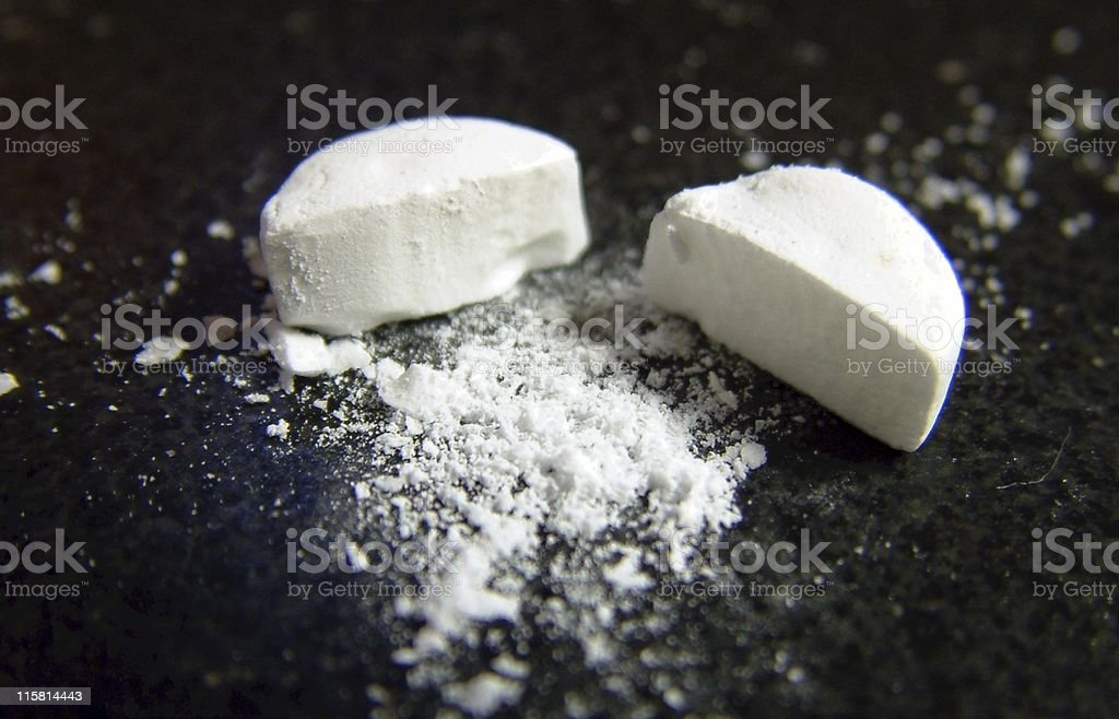 Pill (2) Cut in half, a bit of powder in the middle. Addiction Stock Photo
