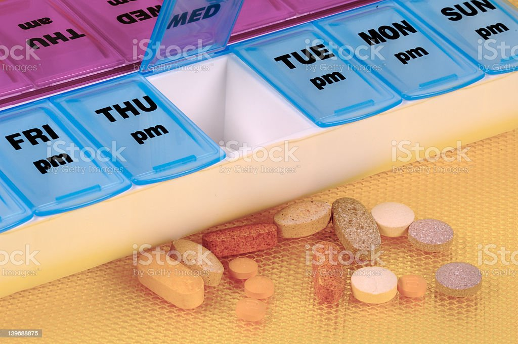 Pill portable with Wednesday open and pills spilled royalty-free stock photo