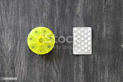 the pillbox for organization of daily medication on gray vintage wooden background