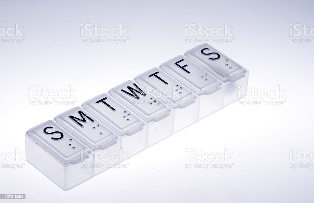 Pillbox with daily doses in compartments stock photo