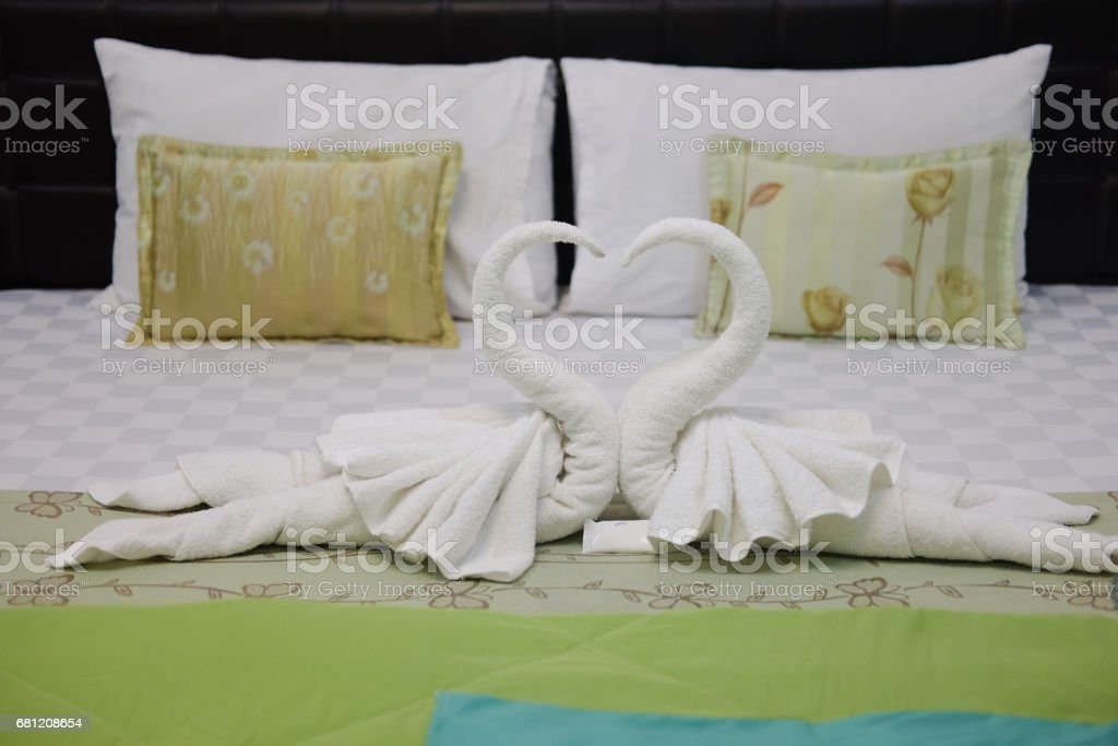Pillow and blown pillow and fold the towel as a swan kiss each other on the white bed in bedroom royalty-free stock photo