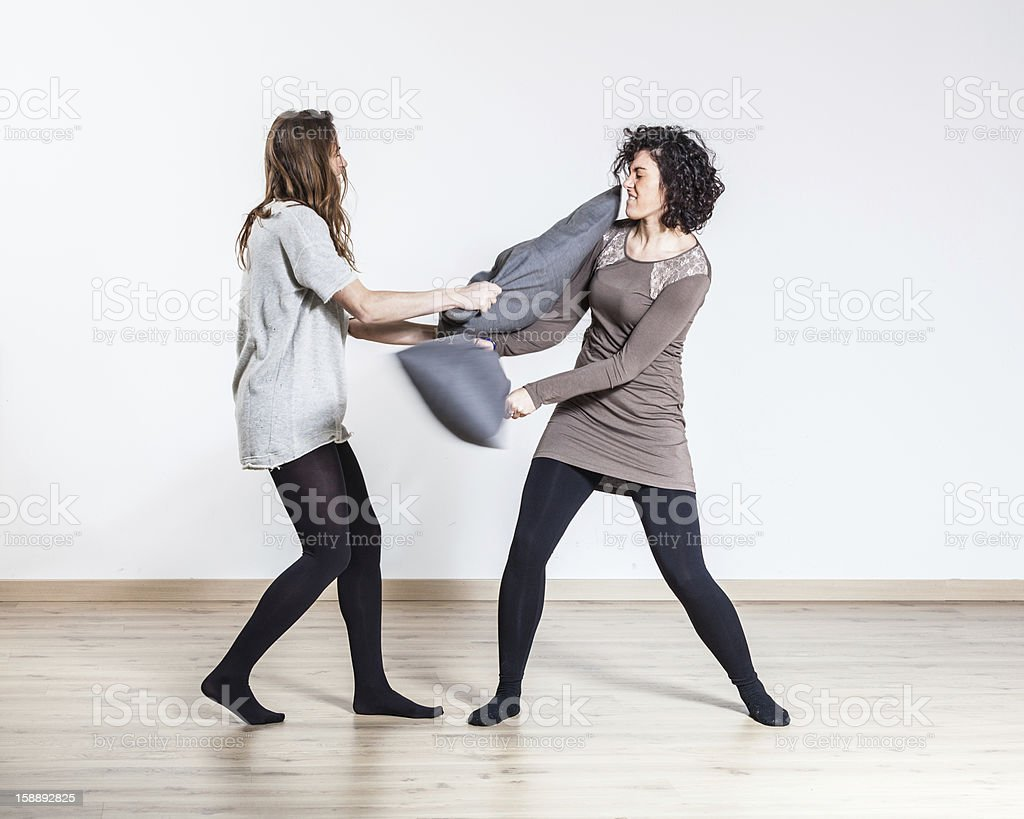 Pillow Fight between Two Beautiful Women royalty-free stock photo