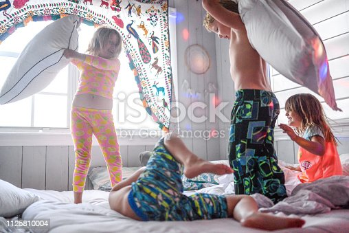 A disco pillow fight, dance party, sleepover with a bunch of elementary age kids, laughing, being rowdy and jumping around on a bed in a domestic home. Kids are being kids in a candid, real life, chaotic, but cheerful and happy scene.