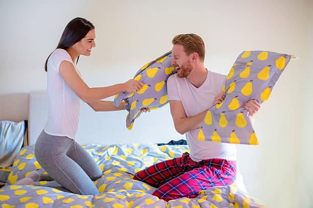 pillow fight in bed - kissenschlacht paar stock-fotos und bilder