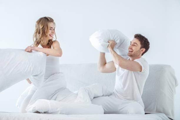 pillow fight - kissenschlacht paar stock-fotos und bilder