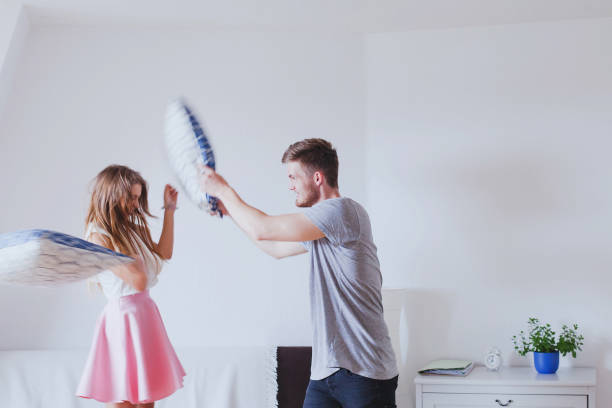 pillow fight, young happy family couple at home - kissenschlacht paar stock-fotos und bilder