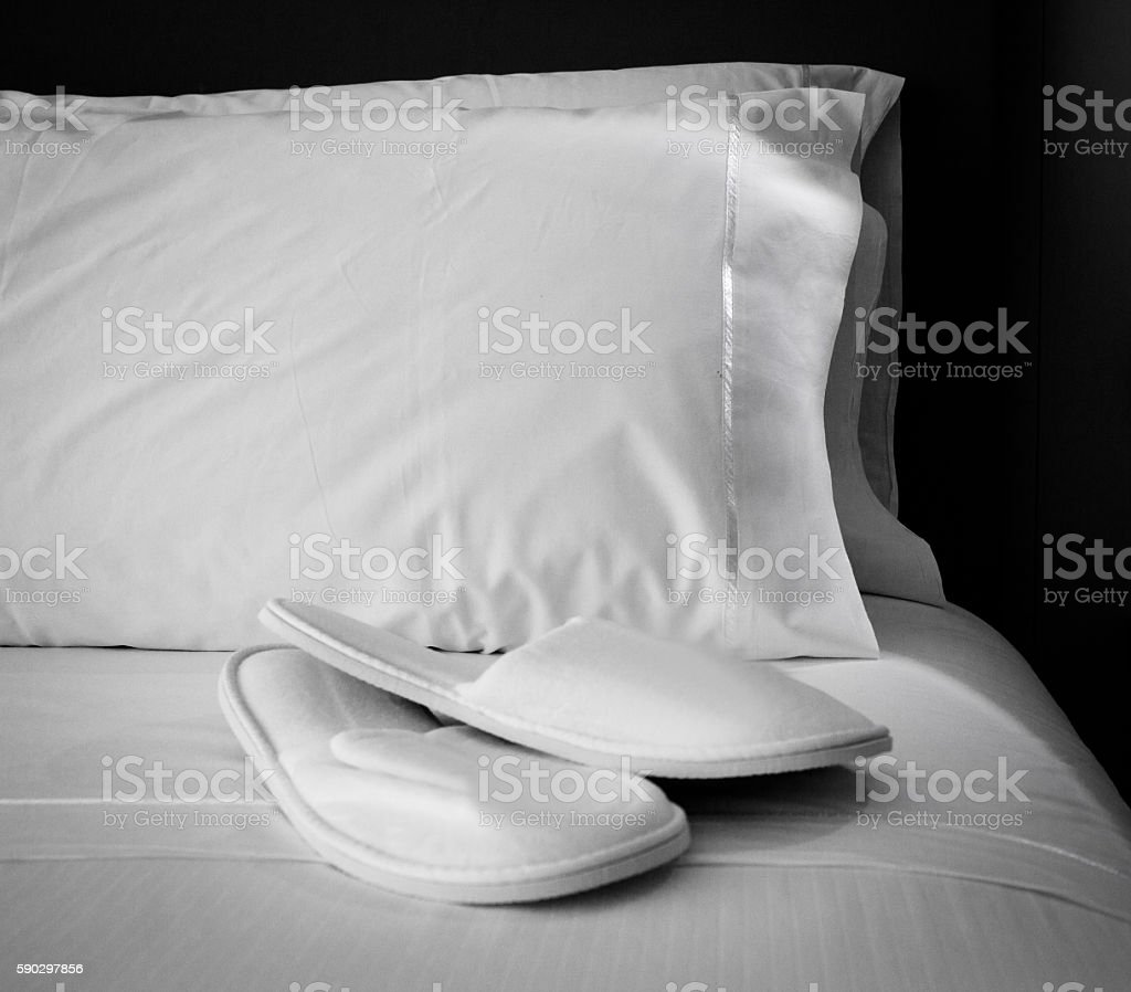 Pillows and slippers on bed royaltyfri bildbanksbilder
